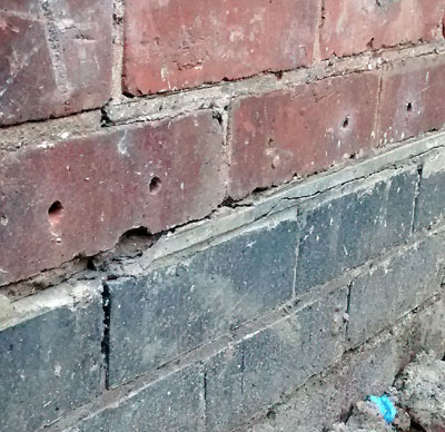 Chemical Damp Proof Course holes in a brick wall, just above the original  slate DPC
